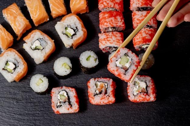 Zestaw Rolek Sushi Na Czarnym Tle łupków Jedzenie Ryba Philadelphia Japoński łosoś Pyszne Sushi Ryżowy Ogórek Posiłek Tradycyjny Wasabi świeże Zdrowe Wyśmienite Dania Surowe. Premium Zdjęcia