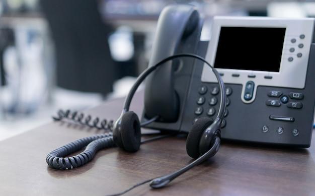 Zestaw słuchawkowy i urządzenia telefoniczne z tłem kopii przestrzeni na biurku w pokoju operacji Premium Zdjęcia
