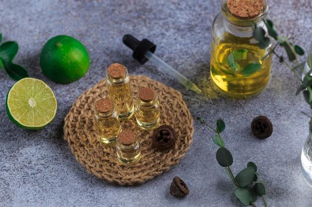 Zestaw Szklanych Butelek Z Olejkiem Eukaliptusowym Na Szarym Stole Pozostawia W Wazonie Premium Zdjęcia