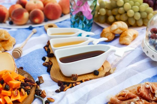Zestaw Trzech Białych Sosboats Ze Słodkim Miodem Na Drewnianej Tacy Na Jedzenie Piknikowe Rozłożyć Tło Premium Zdjęcia