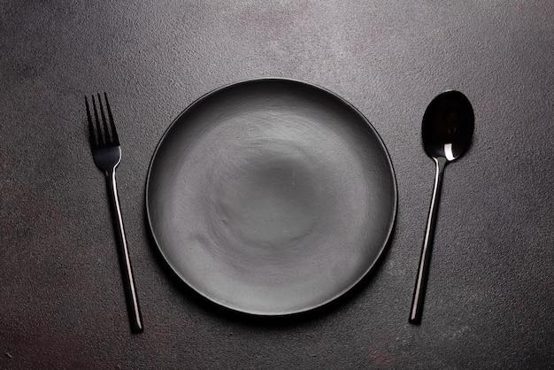 Zestaw Zastawy Stołowej Gotowy Do Posiłku Z Miejsca Kopiowania Czarny. Metalowy Nóż, Widelec, łyżka I Talerz Premium Zdjęcia