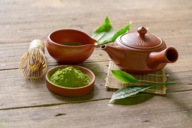 Zestaw zielonej herbaty matcha i japońskiej herbaty. ceramiczny czajniczek i parująca filiżanka na drewnianym tle Premium Zdjęcia