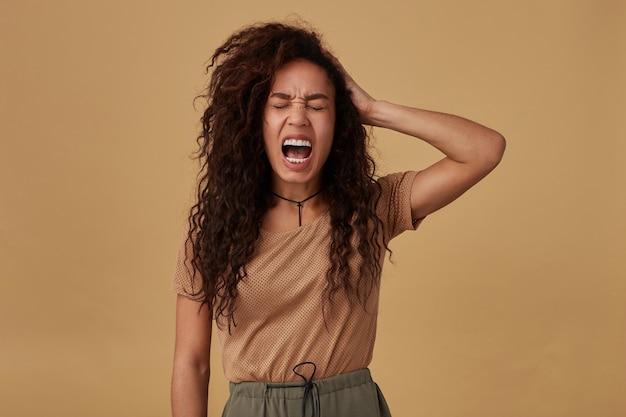 Zestresowana Młoda Brązowowłosa, Kręcona Ciemnoskóra Dama Marszcząca Brwi, Krzycząca I Podnosząca Emocjonalnie Dłoń Do Głowy, Pozując Na Beżu Darmowe Zdjęcia