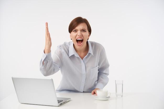 Zestresowana Młoda Krótkowłosa Brunetka Kobieta Z Przypadkową Fryzurą, Krzycząca Gniewnie I Unosząca Emocjonalnie Rękę, Ubrana W Niebieską Koszulę, Pozując Na Biało Darmowe Zdjęcia