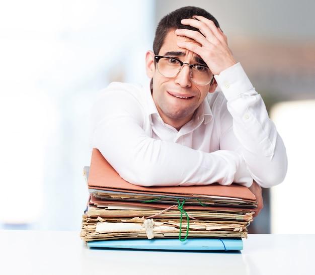 Zestresowany Człowiek Patrząc Na Stos Papierów Z Jednej Strony Na Czole Darmowe Zdjęcia
