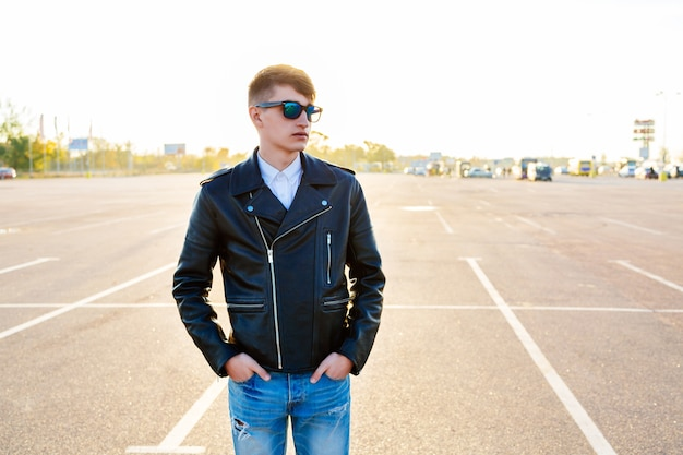 Zewnątrz Jesień Moda Portret Stylowy Mężczyzna Pozuje Na Parkingu W Mieście, Ubrany W Czarną Skórzaną Kurtkę Motocyklową Dżinsy I Okulary Przeciwsłoneczne. Darmowe Zdjęcia