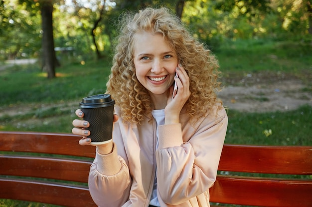Zewnątrz Portret Młodej Pięknej Kobiety Blondynka Siedzi Na ławce W Parku, Pijąc Kawę, Rozmawiając Z Kimś Przez Telefon Darmowe Zdjęcia