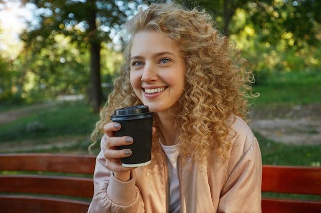 Zewnątrz Portret Młodej Pięknej Kobiety Blondynka Siedzi Na ławce W Parku, Pijąc Kawę Darmowe Zdjęcia