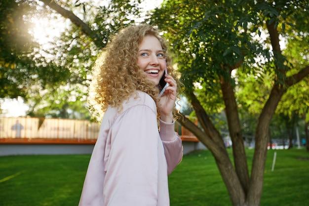 Zewnątrz Portret Pięknej Atrakcyjnej Uroczej Kręcone Włosy Młoda Kobieta Przechodzi Obok, Rozmawiając Z Kimś Przez Telefon Darmowe Zdjęcia