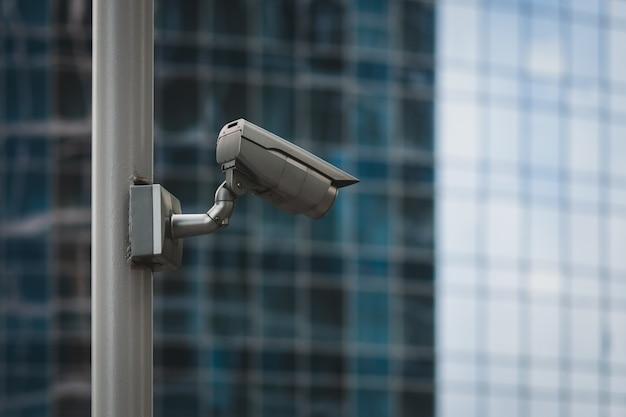 Zewnętrzna Kamera Bezpieczeństwa Na Słupie Przed Szklaną ścianą Budynku Premium Zdjęcia
