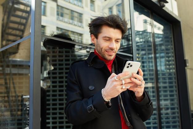 Zewnętrzne Zdjęcie Młodego Brązowowłosego Nieogolonego Faceta Trzymającego Telefon Komórkowy W Uniesionych Rękach I Pozytywnie Wyglądającego Na Ekranie, Stojąc Na Tle Miasta Darmowe Zdjęcia