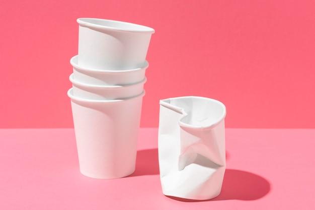 Zgnieciony Plastikowy Kubek I Stos Papierowych Kubków Premium Zdjęcia