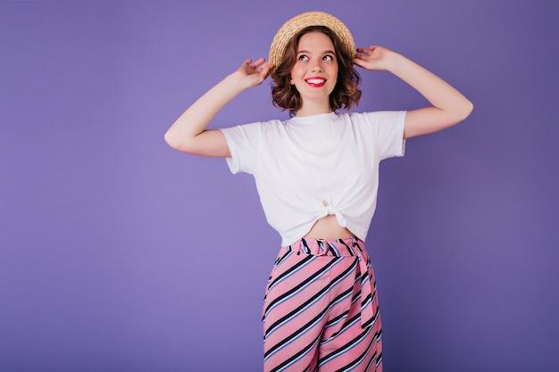 Zgrabna Dama W Białej Koszulce I Kapeluszu Vintage Pozuje Z Uśmiechem. Kryty Zdjęcie Zadowolony Europejskiej Dziewczyny W Pasiaste Spodnie Na Białym Tle Na Jasnej Fioletowej ścianie. Darmowe Zdjęcia