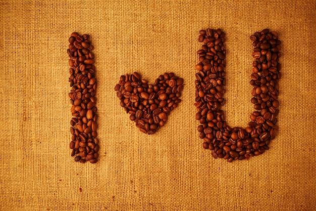Ziarna kawy kocham cię na zwolnionym tle Premium Zdjęcia