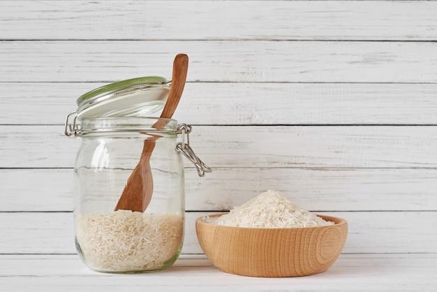 Ziarna Ryżu W Drewnianej Misce I Szklanym Słoju Premium Zdjęcia