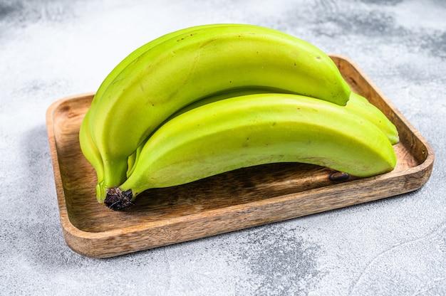 Zieleni Banany Na Drewnianej Tacy. Szare Tło. Widok Z Góry. Owoc Tropikalny Premium Zdjęcia