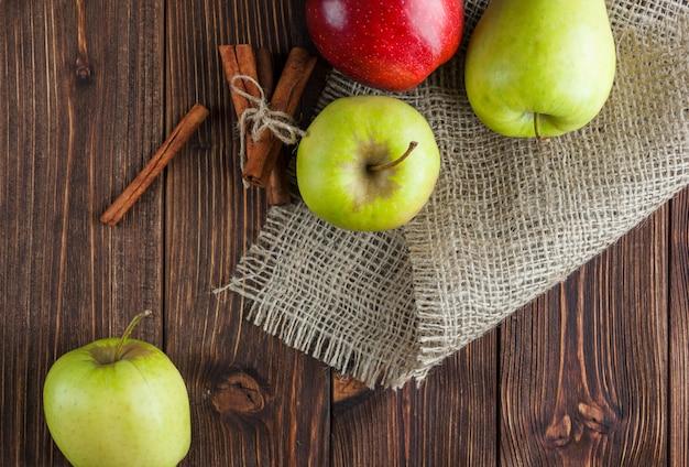 Zieleni Jabłka Z Czerwienią Jeden I Suchy Cynamonowy Odgórny Widok Na Drewnianym Tle I Worze Darmowe Zdjęcia