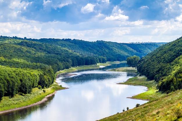 Zielona dolina w lecie z lasami na wzgórzach i wielką rzeką poniżej Premium Zdjęcia