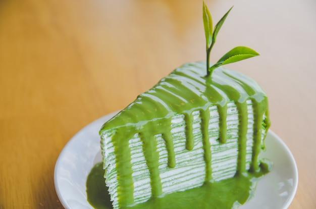 Zielona Herbata Krepa Tort Na Białym Talerzu Na Drewnianym Stole Premium Zdjęcia