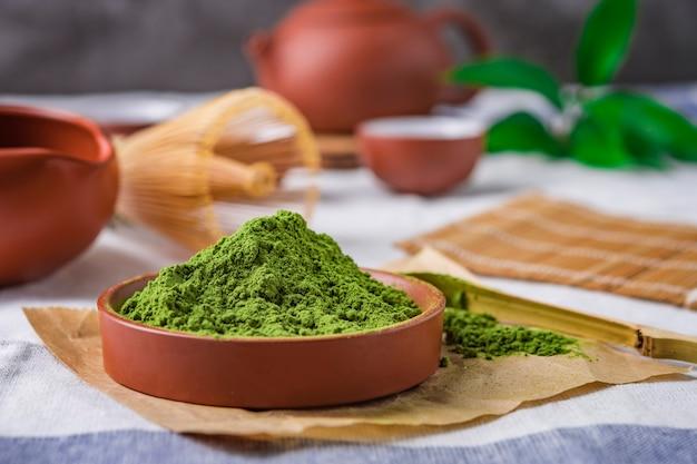 Zielona herbata w proszku z liściem w ceramicznym naczyniu na stole, japońska trzepaczka wykonana z bambusa na ceremonię macha Premium Zdjęcia