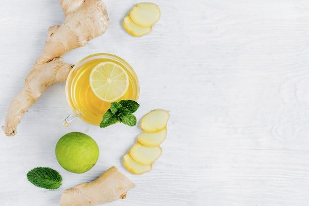 Zielona Herbata Z Imbirem, Miętą I Limonką Na Białym Drewnianym Stole Premium Zdjęcia