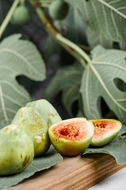 Zielone Figi Na Desce Otoczonej Liśćmi, Selektywne Focus. Darmowe Zdjęcia
