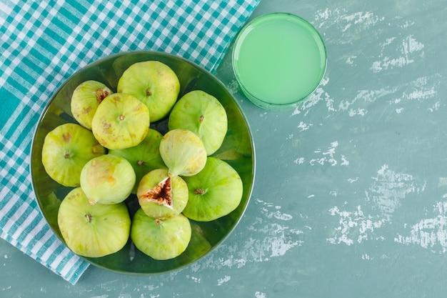 Zielone Figi Na Talerzu Z Napojem Leżą Płasko Na Tynku I Szmatce Piknikowej Darmowe Zdjęcia