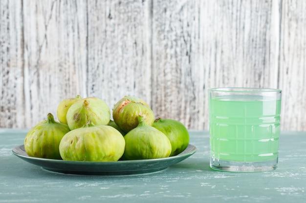 Zielone Figi W Talerzu Z Widokiem Z Boku Napoju Na Tynku I Drewnianym Stole Darmowe Zdjęcia