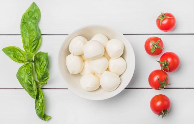 Zielone świeże Liście Bazylii I Czerwone Pomidory Z Miską Kulek Sera Mozzarella Premium Zdjęcia