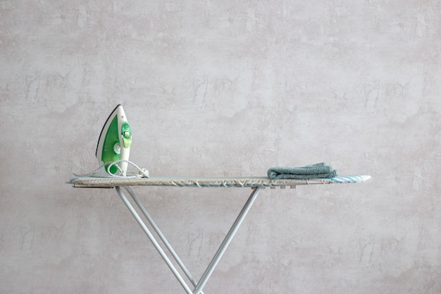 Zielone żelazko Stoi Na Desce Do Prasowania. Premium Zdjęcia