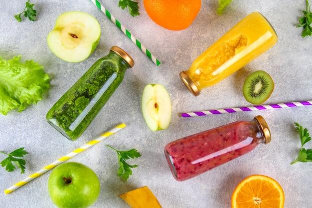 Zielone, żółte, fioletowe koktajle w butelkach porzeczki, pietruszka, jabłko, kiwi, pomarańcza na szarym stole. Premium Zdjęcia