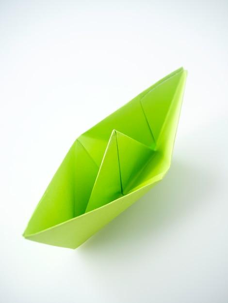 Zielonego papieru łódź kłaść na białym tle. Premium Zdjęcia