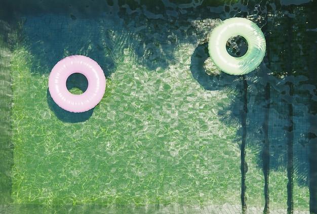 Zielony Basen Na Dnie Widziany Z Góry Z Różowymi I Zielonymi Pływakami I Cieniami Palm. Renderowania 3d Premium Zdjęcia