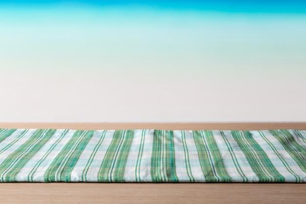 Zielony Obrus Na Stole Z Drewna Przed Tropikalną Plażą Premium Zdjęcia