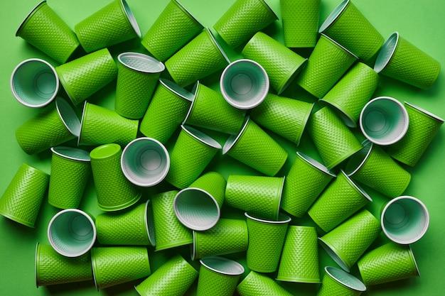 Zielony plastikowy jednorazowy tableware na zielonym tle Premium Zdjęcia