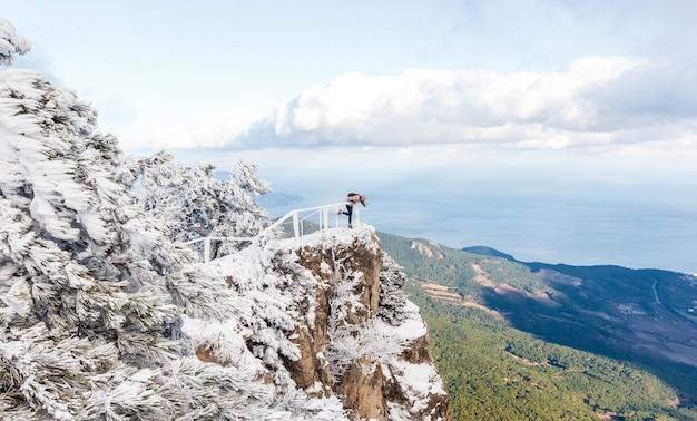 Zima portret yong dziewczyna przy śnieżnym lasem. śnieżny lanscape na szczycie góry Premium Zdjęcia