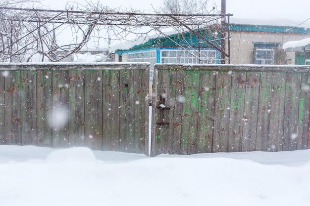 Zima We Wsi. Stary Zniszczony Chwiejny Płot Z Desek. Wokół Dużo śniegu Premium Zdjęcia