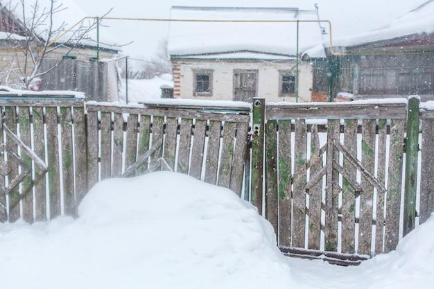 Zima We Wsi, Stary Zniszczony, Rozklekotany Płot Z Desek, Wokoło Dużo śniegu Premium Zdjęcia