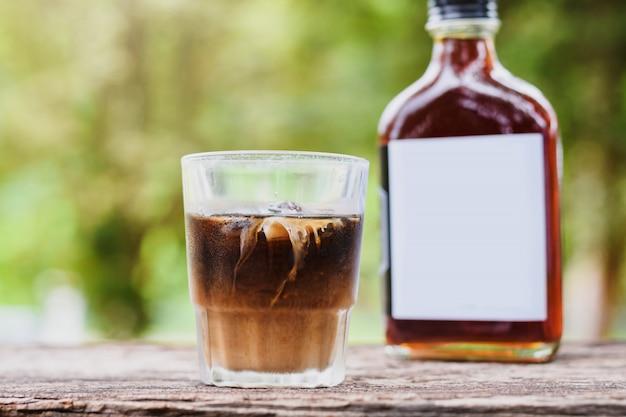 Zimna Kawa Z Mlekiem Na Stole Na Zewnątrz Z Kawą Na Zimno W Szklanej Butelce Na Wynos Premium Zdjęcia