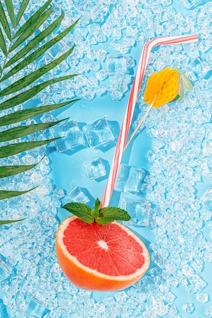 Zimny napój. lód na jasnoniebieskim tle ułożonym w formie kieliszka z rurką na koktajl i plasterek grejpfruta Premium Zdjęcia