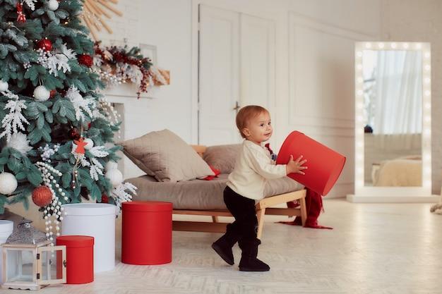 Zimowe Dekoracje świąteczne. Ciepłe Kolory. Piękna Mała Dziewczynka Bawić Się Z Teraźniejszymi Pudełkami Darmowe Zdjęcia
