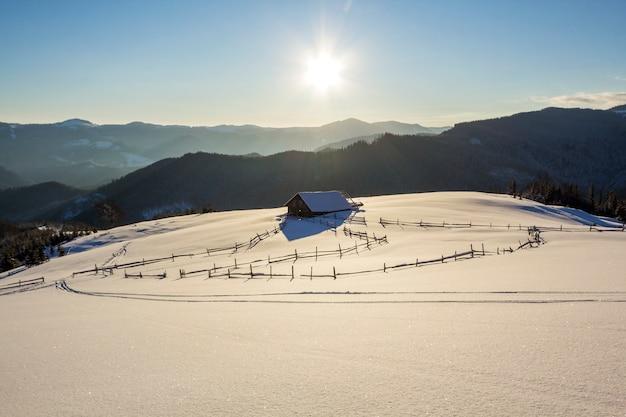 Zimowe święta Krajobraz Górskiej Doliny W Mroźny Słoneczny Dzień. Stara Drewniana Opuszczona Chatka Pasterska W Białym Głębokim Czystym śniegu, Drzewny Ciemny Grzbiet Górski, Jasne Słońce Premium Zdjęcia
