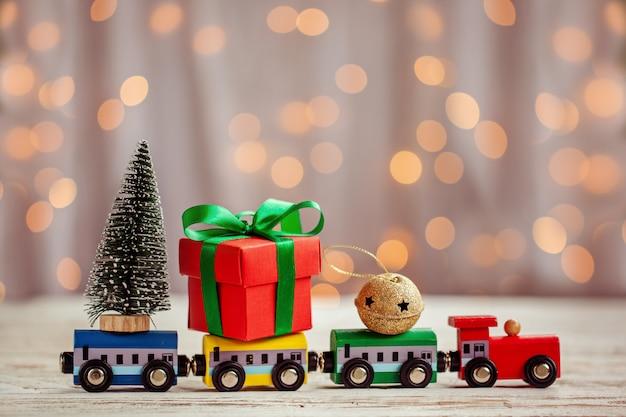 Zimowe tło boże narodzenie miniaturowy kolorowy pociąg z jodły. karta z pozdrowieniami świątecznymi Premium Zdjęcia