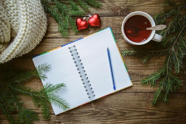 Zimowe zdjęcie świąteczne: notatnik z długopisem, filiżanka herbaty, gałązki jodły, zabawkowe serca i szalik Premium Zdjęcia