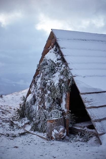 Zimowy Krajobraz. Małe Drewniane Schronisko W Górach Premium Zdjęcia