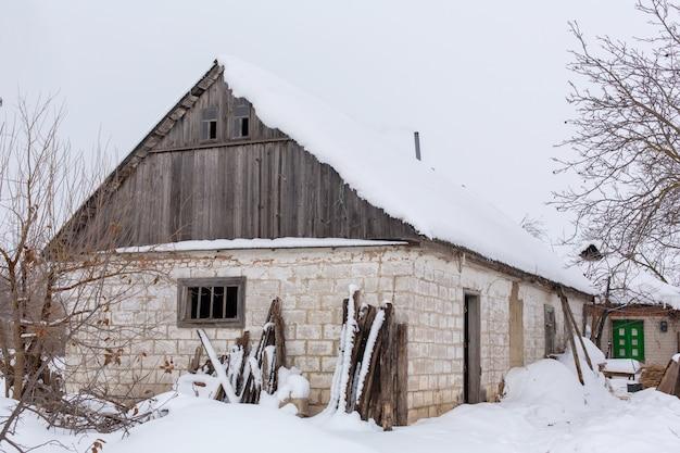 Zimowy krajobraz wsi, zrujnowany opuszczony zniszczony budynek pokryty śniegiem. Premium Zdjęcia