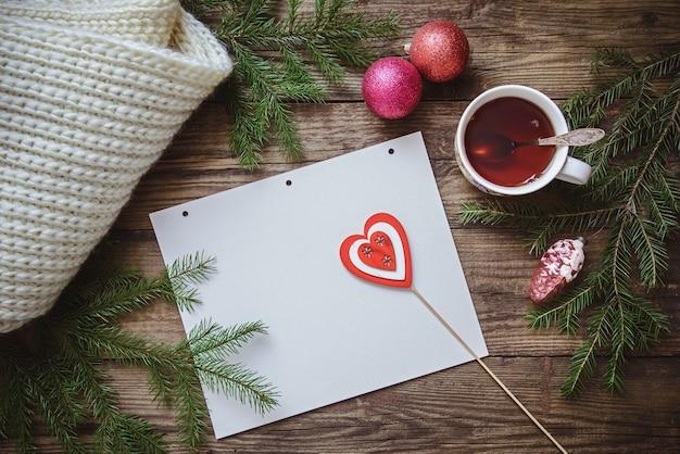 Zimowy obraz: filiżanka herbaty, gałęzie jodły, ozdoby świąteczne, szalik i kartka papieru z sercem na patyku Premium Zdjęcia