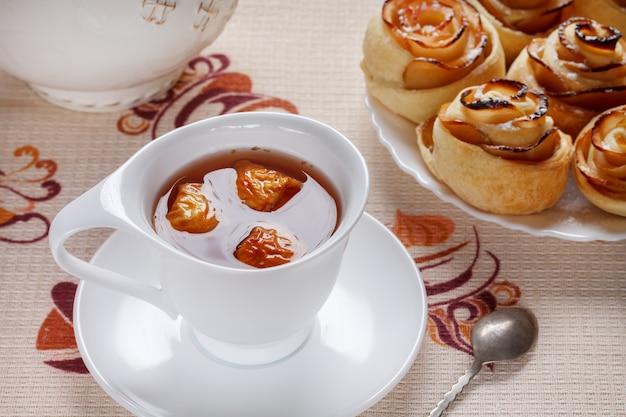 Ziołowa Herbata Jabłkowa W Białej Filiżance Ze Spodkiem I Rumianymi Bułeczkami Na Premium Zdjęcia