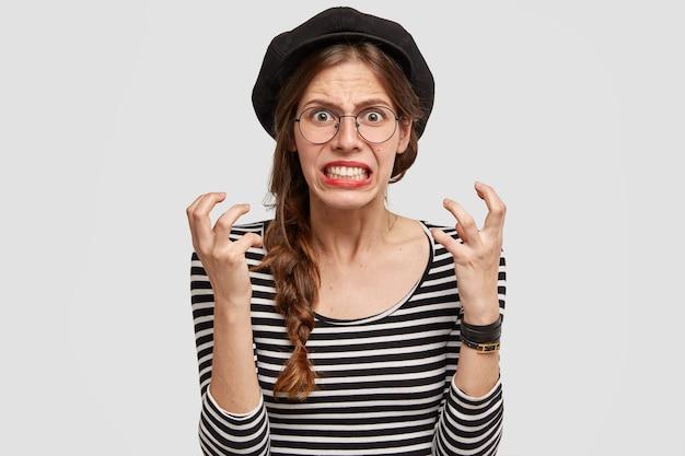 Zirytowana Nauczycielka Francuskiego Zaciska Zęby I Gestykuluje Ze Złością, Patrzy Niecierpliwie, Ma Negatywny Wyraz Twarzy, Nosi Beret, Pozuje Nad Białą ścianą Darmowe Zdjęcia