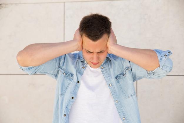 Zirytowany młody człowiek obejmujące uszy rękami w ścianie na zewnątrz Darmowe Zdjęcia